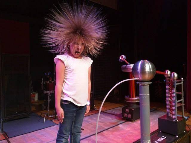 A child stands on top of a voltage multiplier and her hair is sticking straight up while she makes a funny face.