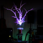 A picture of ArcAttack's Thundermouse Tesla coil kit making very large sparks setup in a living room. There are musical instruments on the wall and test equipment setup on the tables.