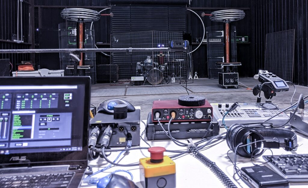 ArcAttack's broadcast station with various computer screens and pieces of audio equipment strewn about.