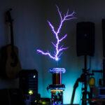 Thundermouse DIY Tesla coil kit making giant lightning bolts in a living room setting.