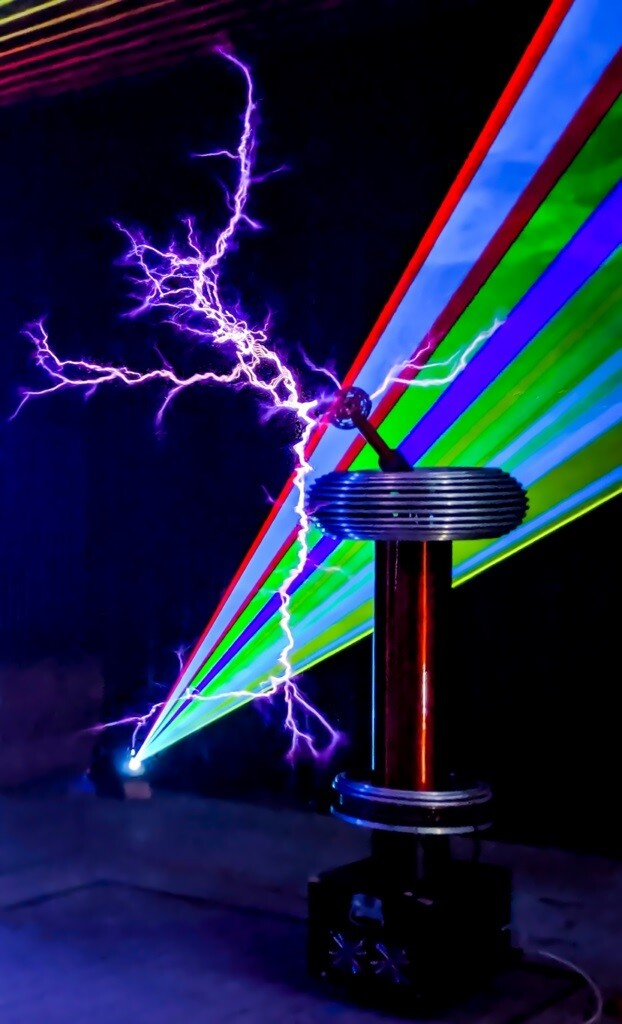 A Tesla coil emits a giant lightning bolt while a laser projects a rainbow pattern in the background.