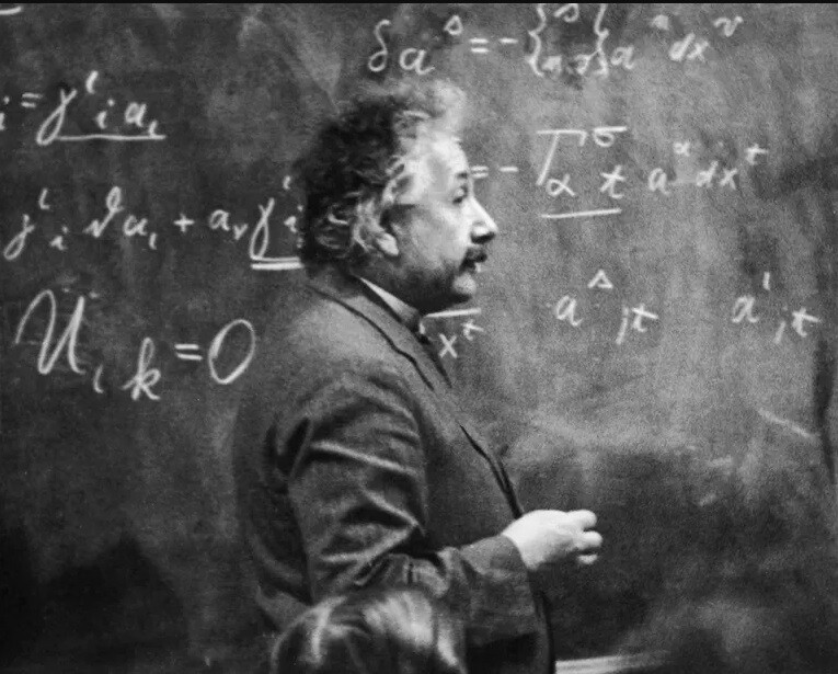 Einstein stands in front of a chalkboard full of equations.