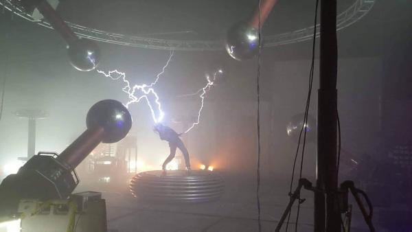 5 Tesla coils zapping an ArcAttack performer as she stands on a platform.